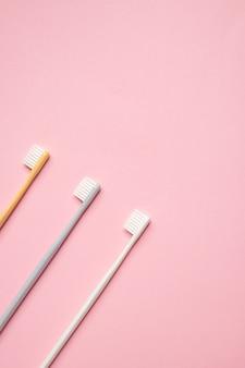 분홍색 배경에 회색과 흰색 칫솔. 치아, 치과 개념 돌보기. 평평한 사진, 복사 공간, 평면도.