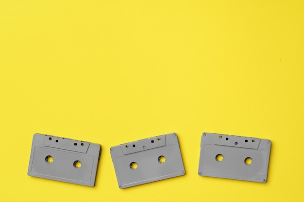 Gray audio cassette on yellow background top view, copy space