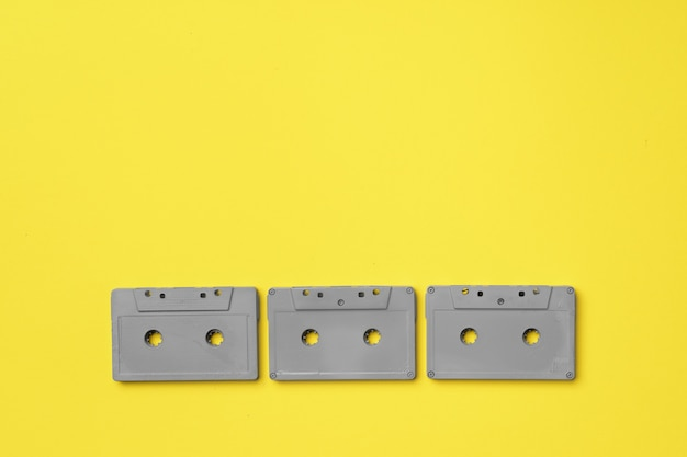 Gray audio cassette on yellow background top view