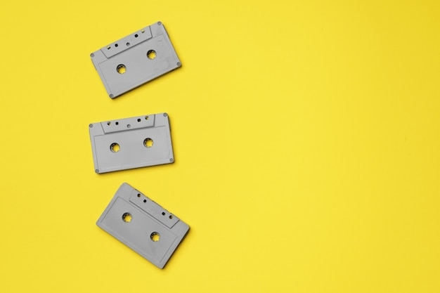 Gray audio cassette on yellow background