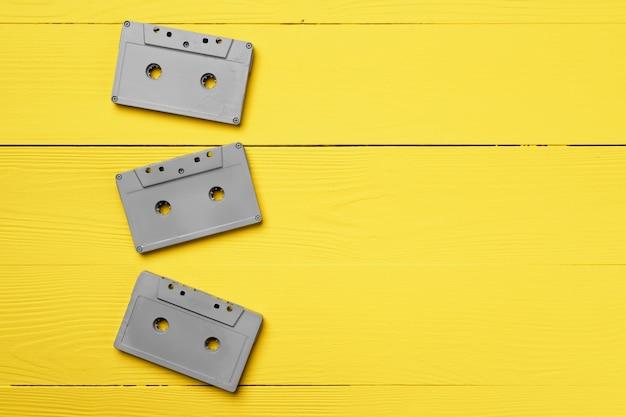 黄色の背景上面図、コピースペースに灰色のオーディオカセット
