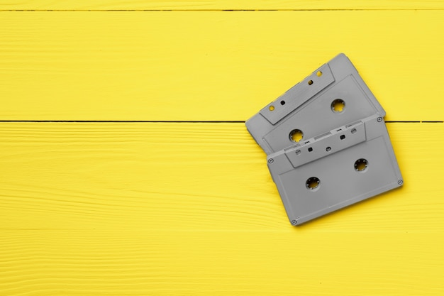 Gray audio cassettes on yellow background top view, copy space