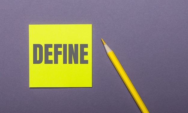 On a gray background, a bright yellow pencil and a yellow sticker with the word define
