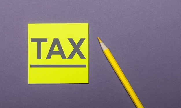 On a gray background, a bright yellow pencil and a yellow sticker with the word tax