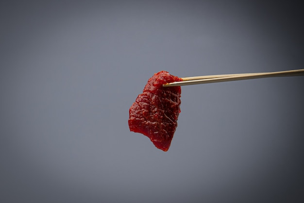 Gray background and holds raw meat with chopsticks