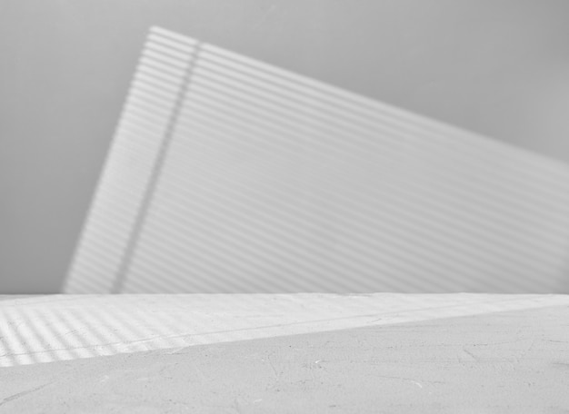 Gray background for product presentation with window light through blinds
