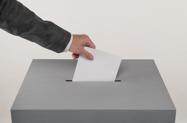 회색 투표함 대통령 선거 유권자가 투표함에 투표용지를 던집니다.