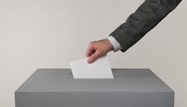 회색 투표함 대통령 선거 유권자는 투표함에 투표용지를 던집니다.