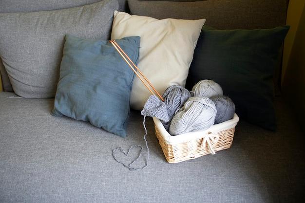 Серые клубки шерсти и спицы в плетеной корзине на сером диване