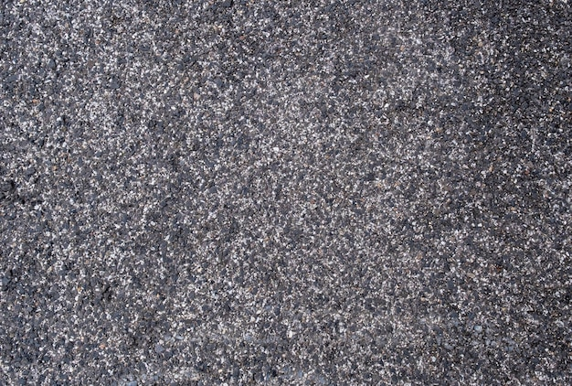 Gray and black background with mixture of dark bituminous pitch with sand or gravel for surfacing roads, flooring, roofing.