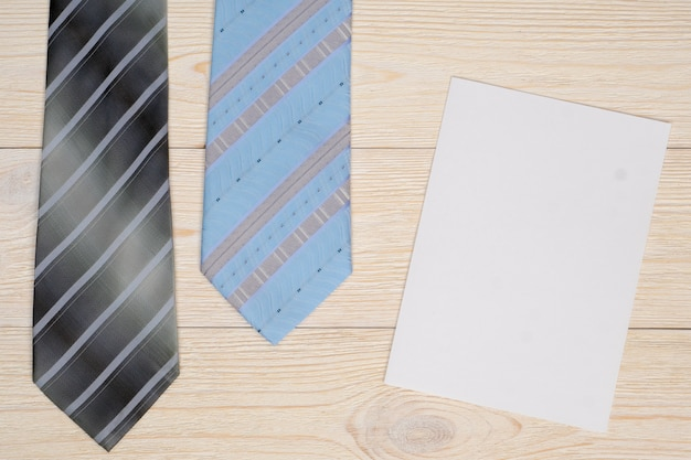 Gray and blue neck ties with empty paper sheet on workbench