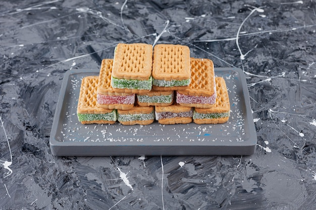 Un bordo grigio di cialde dolci posto su una superficie di marmo