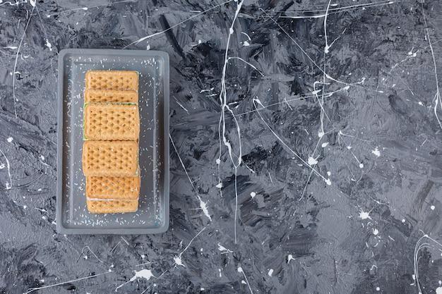 Un bordo grigio di cialde dolci posto su un marmo.