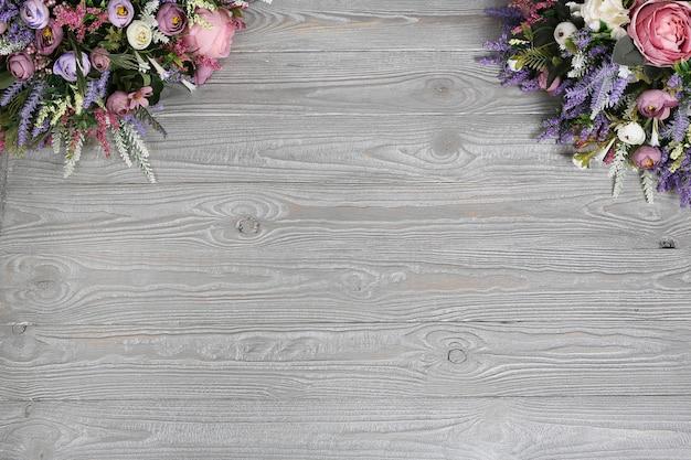 花と灰色のボード。フレームの隅にある花の花束と木質の質感を持つ灰色の背景。