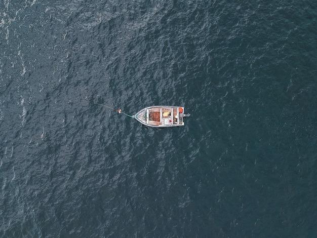 昼間の水の体に灰色のボート