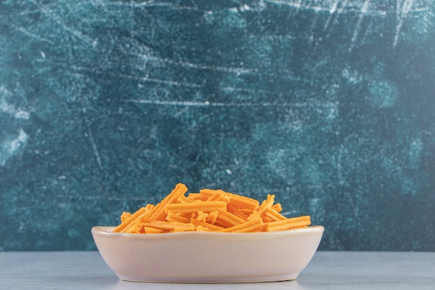 Gray bowl of crispy crackers placed on stone background.