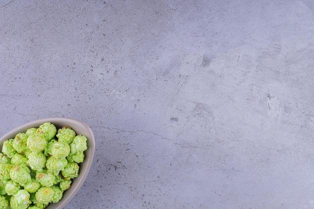 Ciotola grigia piena di caramelle popcorn su sfondo marmo. foto di alta qualità