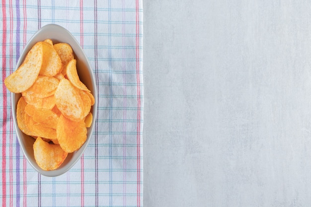 Gray bowl full of spicy potato chips on stone.