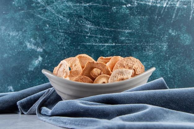 Ciotola grigia di anelli di mela essiccati sani su fondo di pietra.
