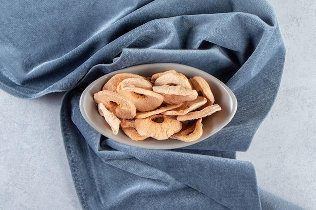 Ciotola grigia di anelli di mela essiccati sani sulla pietra.