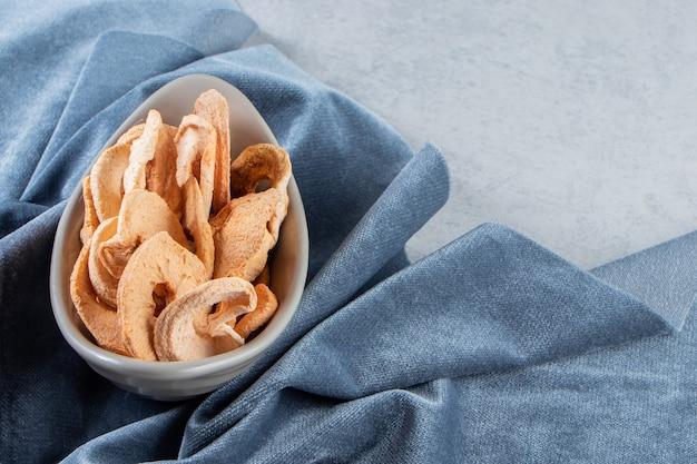 돌 배경에 건강에 좋은 말린 사과 반지의 회색 그릇.
