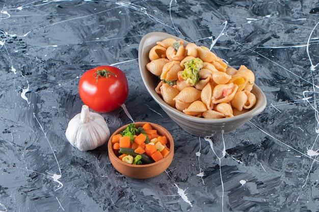 Серая миска вкусных макаронных изделий из ракушек с мини-салатом на мраморной поверхности.