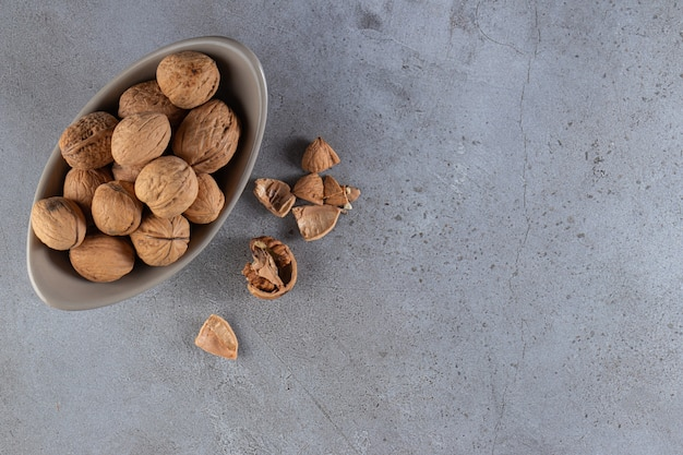 Gray bowl of organic shelled walnuts on stone background.
