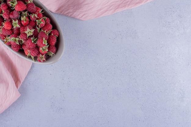 Ciotola grigia rifornita di lamponi su fondo marmo. foto di alta qualità