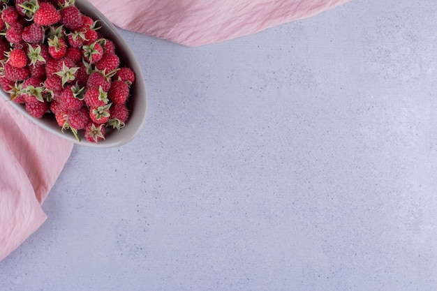 Серая миска с малиной на мраморном фоне. фото высокого качества