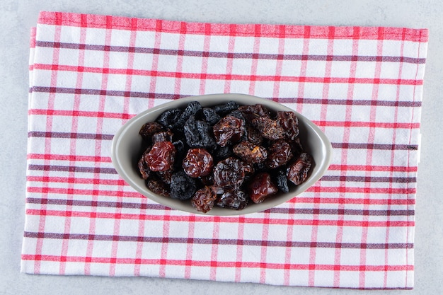 Gray bowl of tasty dried dates on striped tablecloth.