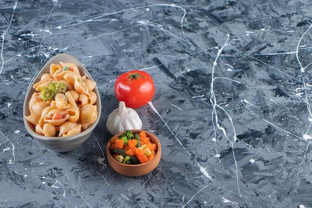 Ciotola grigia di gustosa pasta di conchiglie con mini insalata su superficie di marmo.