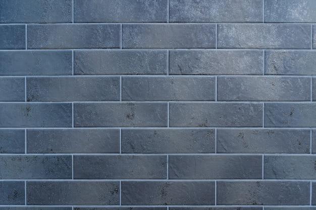 灰色のレンガの壁。白い詰物とレンガの質感