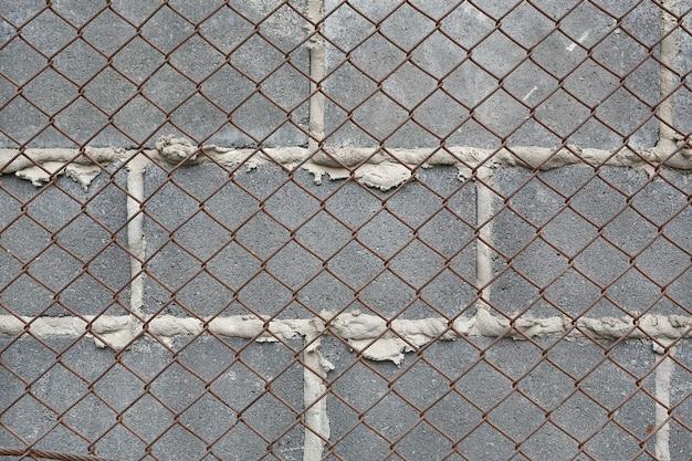 Gray brick wall with iron grating.