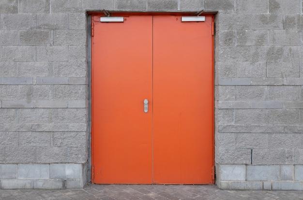 写真の中央に広く明るいオレンジ色のドアが付いている灰色のレンガの壁。建物に入る