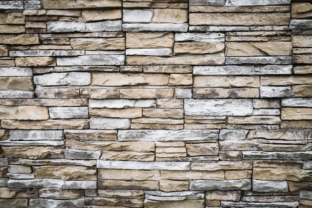 灰色がかった茶色のレンガの壁。石のテクスチャ、背景