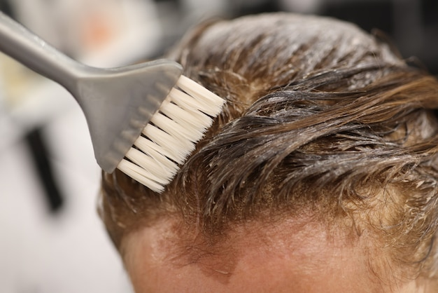 Gray brush apply hair dye to head close up.