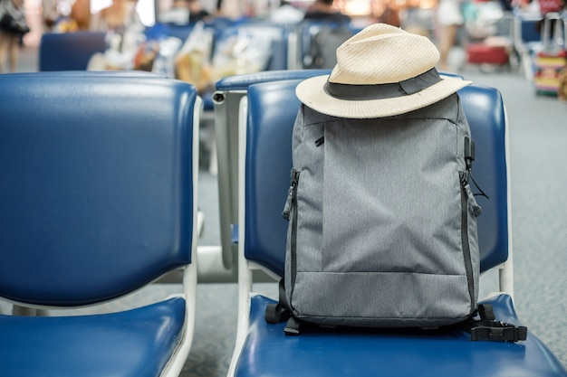 Gray business backpack with hat on seat at the interior of airport terminal. business and travel concept
