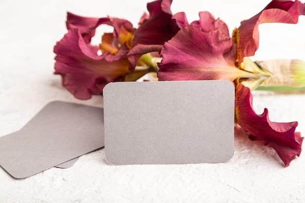 흰색 콘크리트 바탕에 아이리스 부르고뉴 보라색 꽃이 있는 회색 명함. 측면보기