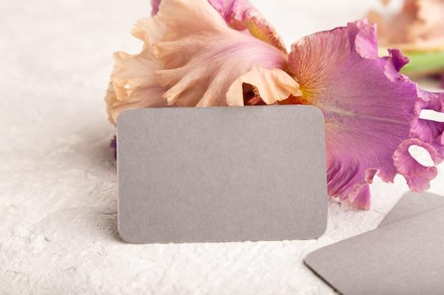 흰색 콘크리트 바탕에 아이리스 보라색 꽃이 있는 회색 명함. 측면보기, 복사 공간