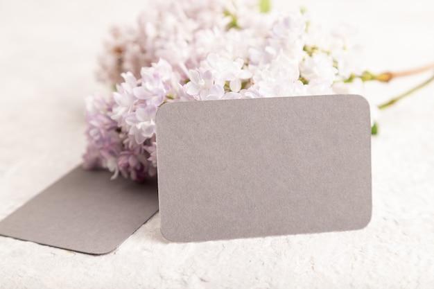 회색 콘크리트 배경에 라일락 꽃이 있는 회색 명함. 측면보기, 복사 공간,
