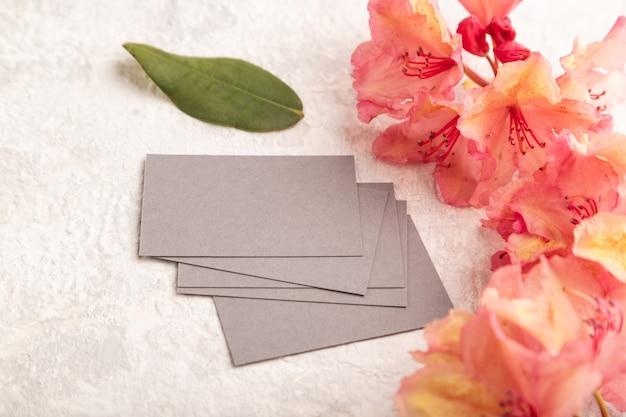 灰色のコンクリートの背景にピンクのツツジの花と灰色の名刺。側面図、コピースペース
