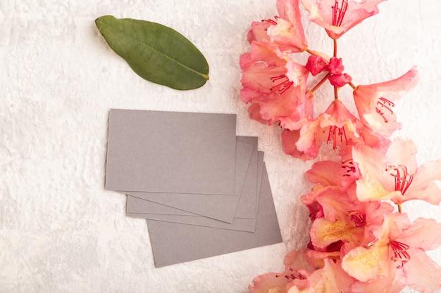 灰色のコンクリートの背景にピンクのツツジの花と灰色の名刺。上面図、フラットレイ