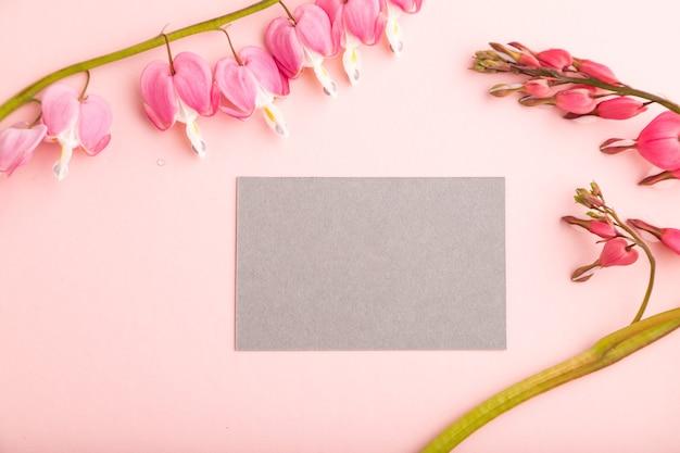 분홍색 디센트라가 있는 회색 명함, 분홍색 파스텔 배경에 깨진 하트 꽃. 평면도