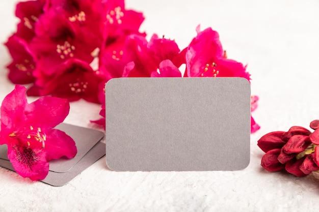 灰色のコンクリートの背景に紫色のツツジの花と灰色の名刺。側面図、コピースペース