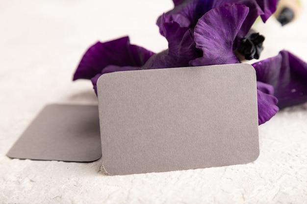 Серая визитная карточка с фиолетовыми цветами ириса на белом фоне бетона. вид сбоку, копировать пространство