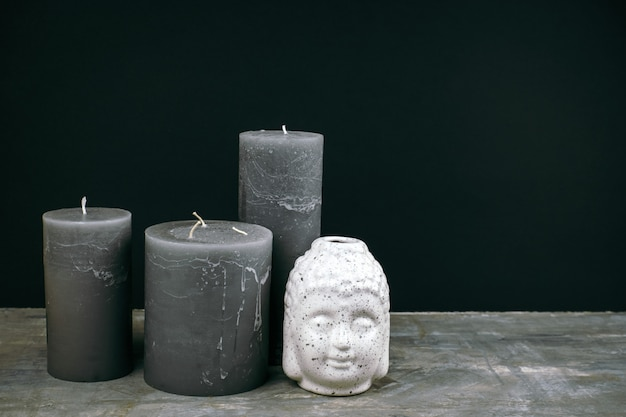 Gray candles and white ceramic buddha head on a table opposite black wall