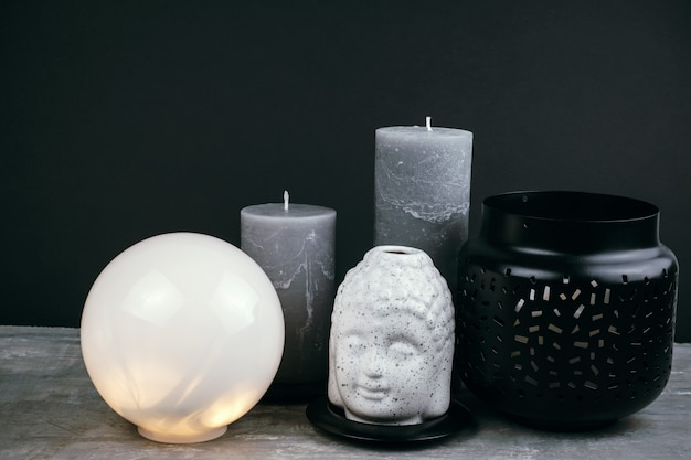 Gray candles, white round lamp and white  ceramic buddha head on a table opposite black wall