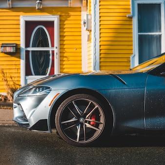Серый автомобиль перед желтым домом