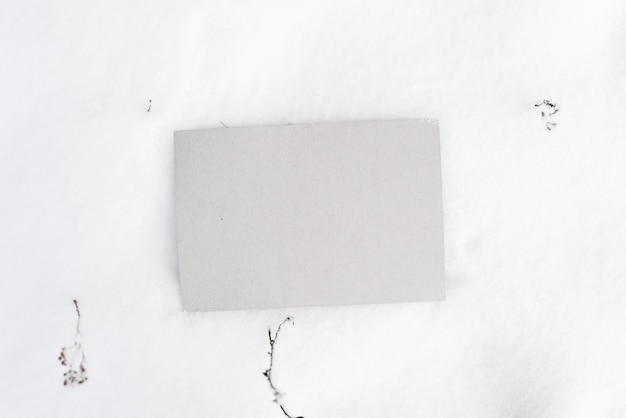 Gray cardboard mock up. blank sheet of cardboard lying in the snow, top view. empty space for text, branding, message.