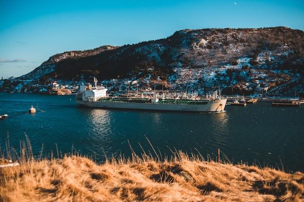 Gray cargo ship docked beside mountain